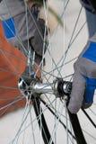 Hände, die Fahrradfelge unter Verwendung des Schlüssels reparieren stockbild