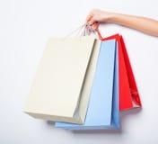 Hände, die farbige Einkaufstaschen auf weißem Hintergrund halten Lizenzfreie Stockfotos