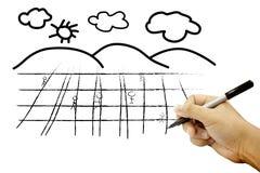 Hände, die Feld und Himmel auf Weißbuch zeichnen Stockbilder