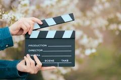 Hände, die Film-Schiefer-Kino-Scharnierventil auf Frühlings-blühendem Hintergrund halten Stockfoto