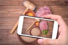 Hände, die Foto rohes Schweinefleischschnitzel mit Smartphone nehmen Stockbilder