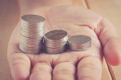 Hände, die Geld mit Retro- Weinleseart des Filtereffektes halten Stockfoto