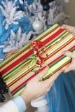 Hände, die Geschenk durch Weihnachtsbaum austauschen Stockfotos