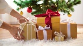 Hände, die Geschenkboxen unter Weihnachtsbaum setzen Stockfotografie