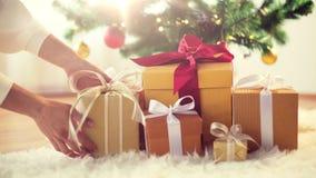 Hände, die Geschenkboxen unter Weihnachtsbaum setzen lizenzfreies stockbild