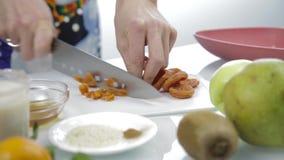 Hände, die getrocknete Aprikosen mit großem Messer auf Schneidebrett hacken Kochen der gesunden Nahrung stock video footage