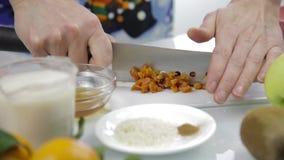 Hände, die getrocknete Aprikosen mit großem Messer auf Schneidebrett hacken Kochen der gesunden Nahrung stock video