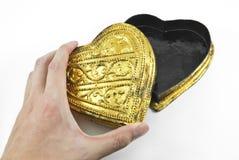 Hände, die goldenes Herz halten Lizenzfreie Stockbilder