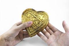 Hände, die goldenes Herz halten Lizenzfreie Stockfotografie
