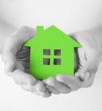 Hände, die Grünbuchhaus halten Stockfoto