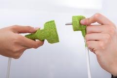 Hände, die grüne Stecker reparieren Stockfotos