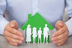Hände, die grünes Musterhaus und Familie schützen Lizenzfreies Stockbild