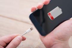Hände, die Handy mit Symbol der schwachen Batterie halten Stockbild