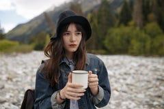 Hände, die heißen Tasse Kaffee oder Tee im Morgensonnenlicht mit buautiful Gebirgshintergrund halten lizenzfreies stockfoto