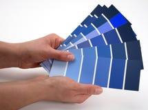 Hände, die heraus eine Auswahl einer Vielzahl der blauen Farbmuster auflockern lizenzfreie stockbilder