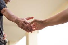Hände, die heraus erreichen, um zusammen zu helfen Lizenzfreie Stockbilder