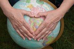 Hände, die Herz über Welt bilden Lizenzfreie Stockbilder