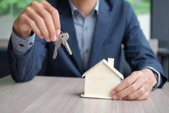 Hände, die Holzhausmodell und -schlüssel halten stockfotografie