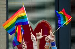 Hände, die homosexuelle Flaggen wellenartig bewegen Lizenzfreies Stockfoto
