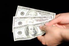 Hände, die hundert Dollar anhalten Stockfoto