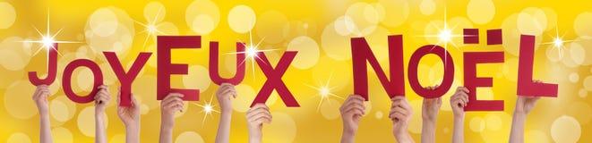 Hände, die Joyeux Noel mit goldenem Hintergrund halten lizenzfreie stockfotos