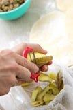 Hände, die Kartoffel mit Schäler abziehen lizenzfreie stockfotos