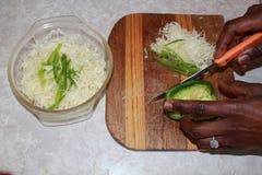 Hände, die Kohl und grünen Paprika hacken Stockfoto