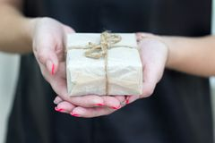 Hände, die Kraftpapiergeschenkbox mit als Geschenk für Weihnachten, neues Jahr, Valentinstag oder Jahrestag auf schwarzem Hinterg Stockbilder