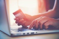 Hände, die Kreditkarte und Laptop halten Stockfotos