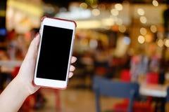 Hände, die leeres Anzeigenmodell des Smartphone beweglich mit Café halten lizenzfreies stockfoto