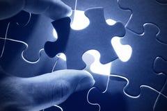Hände, die letztes Stück eines Puzzlespiels platzieren Stockfoto