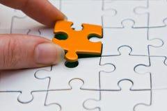 Hände, die Stück eines Puzzlespiels setzen Stockbild