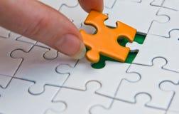 Hände, die Stück eines Puzzlespiels setzen Lizenzfreies Stockfoto