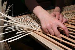 Hände, die manuell Weidengewebe 6 erarbeiten Stockbild