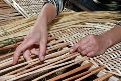 Hände, die manuell Weidengewebe erarbeiten Stockbild