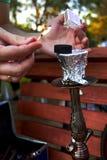 Hände, die Match und brennende Kohle für Huka im Park halten lizenzfreie stockfotos