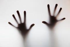 Hände, die Mattglas berühren. Begriffsschrei für Hilfe Stockfotos