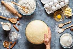 Hände, die mit dem Teigvorbereitungsrezeptbrot, -pizza oder -torte machen ingridients arbeiten Stockfotos