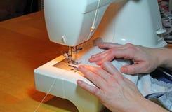Hände, die mit einer Maschine nähen Stockfotos