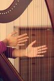 Hände, die mit Harfeninstrument dämpfen Lizenzfreie Stockfotografie