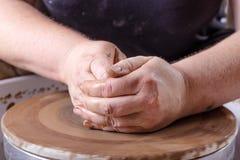 Hände, die mit Lehm auf Töpferscheibe arbeiten Stockfotografie