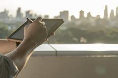 Hände, die morgens Tablettengebäudehintergrund halten stockfotografie