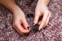 Hände, die Nadel und Knopf halten Lizenzfreies Stockfoto