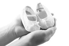 Hände, die neugeborene Babyschuhe anhalten Stockfotos