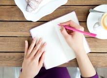 Hände, die am Notizbuch in Café schreiben Stockfoto