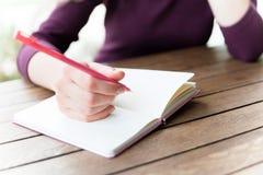 Hände, die am Notizbuch in Café schreiben Lizenzfreies Stockfoto