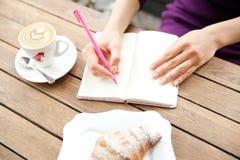 Hände, die am Notizbuch in Café schreiben Lizenzfreie Stockfotos