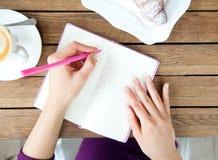 Hände, die am Notizbuch in Café schreiben Stockfotos