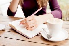 Hände, die am Notizbuch in Café schreiben Lizenzfreie Stockbilder