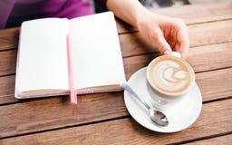 Hände, die am Notizbuch in Café schreiben Stockbild